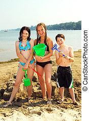 Portrait of group of children on a beach building a sand castle