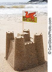 Sandcastle On Beach Flying Welsh Flag
