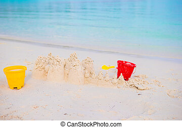 Sandcastle on white beach with plastic kids toys