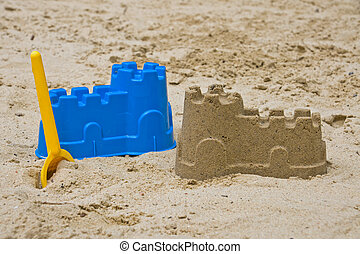 Sandcastle with a yellow shovel