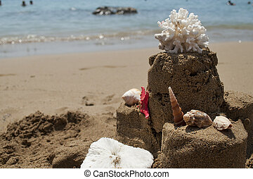 Sandcastle with starfish, coral and seashell on sandy beach