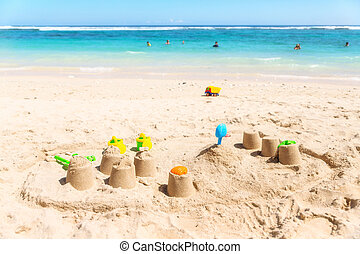Sandcastles on a beach with the sea in the background.