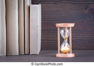 Sandglass, hourglass or egg timer on wooden table showing the last second or last minute or time out