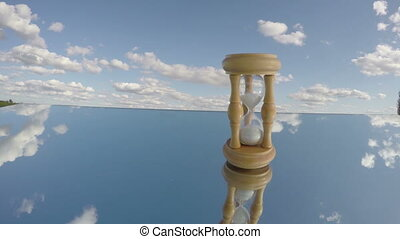 sandglass on mirror and clouds