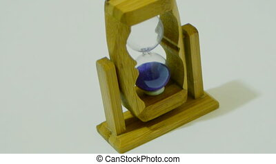 Sandglass with lilac sand on white background