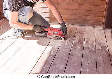 Sanding hardwood floor with the grinding machine. Repair in the apartment, country house,patio. Carpenter doing parquet wood floor polishing maintenance work by grinding machine.Copy space