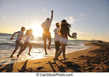 sandstrand, rennender , personengruppe