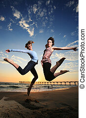 sandstrand, sonnenuntergang, springende , mädels, glücklich