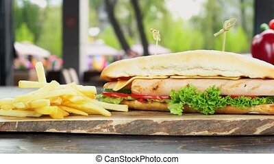 Sandwich and fries close up. Fast food meal, wood board.