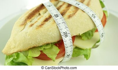 Sandwich and tape measure close up