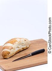 Sandwich bread with knife on the wooden board