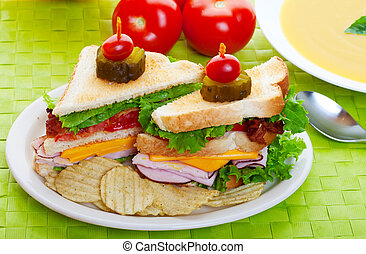 Cub sandwich on a green place mat with yellow soup