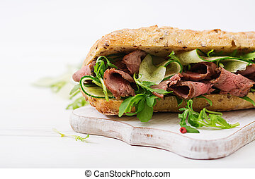 Sandwich of whole wheat bread with roast beef, cucumber and...
