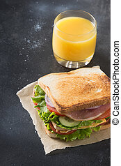 Sandwich with bacon, tomato, onion, salad on black. Close up.