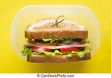 Sandwich with cheese, ham and fresh vegetables in a container on a yellow bright background.