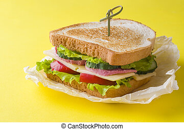Sandwich with cheese, ham and fresh vegetables on a yellow bright background.