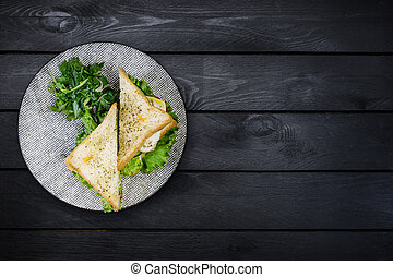 Sandwich with chicken and vegetables on a ceramic plate. On black wooden background. Top view, copy space for your text