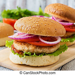 Sandwich with chicken burger, tomatoes, red onion and...