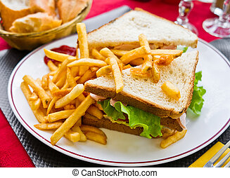 Sandwich with chicken, cheese and golden French fries ...