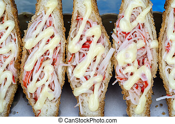 Sandwich with crab sticks and mayonnaise for sell at street food market in Thailand . Tasty sandwich close up