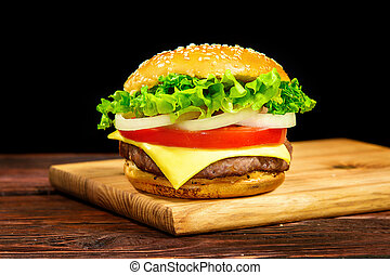 Sandwich with cutlet, cheese, tomato, onion and lettuce on a wooden board