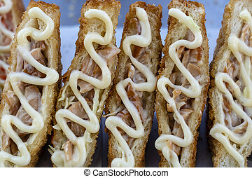 Sandwich with fried bacon and mayonnaise for sell at street food market in Thailand . Tasty sandwich close up