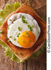 Sandwich with fried egg, ham and cheese close-up on a table vertical top view