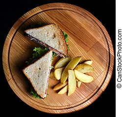 Sandwich with fried potatoes on a wooden board isolated on a black background. Top view. Restaurated food. Fast food.