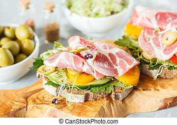 sandwich with ham, olives, rye bread and vegetables