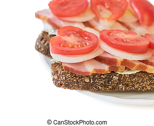 Sandwich with ham, tomato, onion and lettuce.