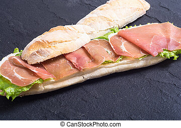 Sandwich with hamon and salad on stone board