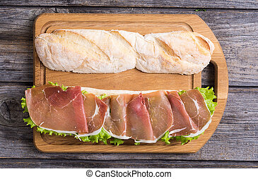 Sandwich with hamon and salad on wooden board