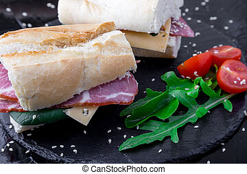 Sandwich with jamon, arugula, tomatoes, cheese on stone slate black background. Close up