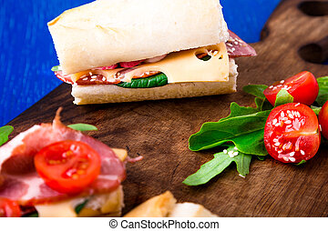 Sandwich with jamon, arugula, tomatoes, cheese on wooden board blue background. Rustic.