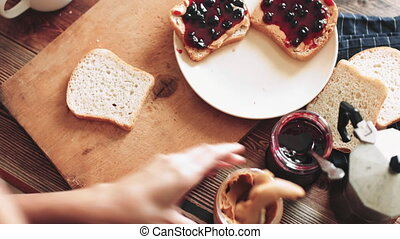 Sandwich with peanut butter and jam. - Hands making a...