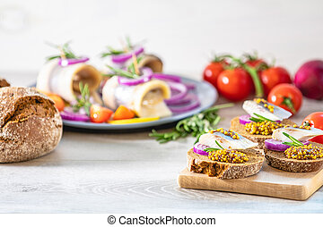 Sandwich with pieces of marinated herring with red onion and...