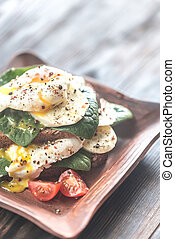 Sandwich with poached eggs, mozzarella, spinach and cherry...