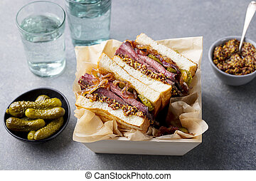 Sandwich with roast beef in wooden box. Grey stone background. Close up.