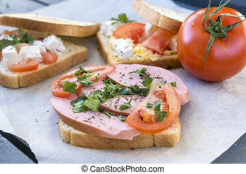 sandwich with sausage ,tomato and herbs