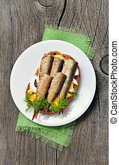 Sandwich with sprats and green onion and egg on white plate