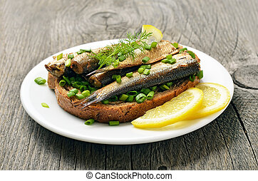 Sandwich with sprats and green onion on white plate