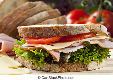 Sandwich with Swiss cheese, ham, tomato and curly lettuce, ...