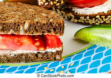Sandwich with tomato and bread on a blue plate.
