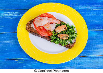 Sandwich with tomato, shrimps, mussels and chopped parsley on a yellow and white plate on a blue wooden background.