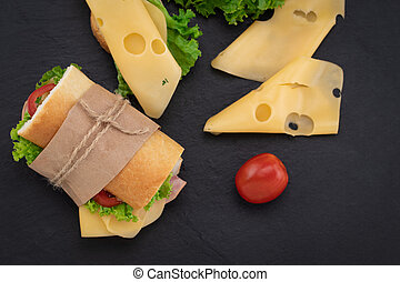 sandwich with with ham, cheese, tomatoes, lettuce on over stone. Top view with copy space