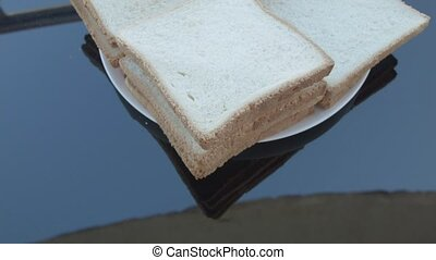 Sandwiches in a white plate on a black mirror table.