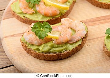 Sandwiches with avocado cream and shrimp on a cutting board.