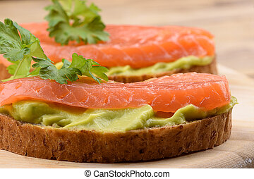 Sandwiches with avocado cream and slices of salmon on a cutting board.