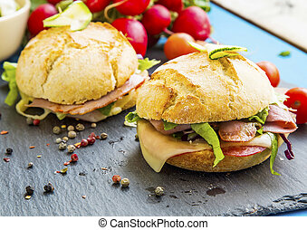 Sandwiches with bacon, cheese, salad and rustic bread