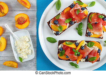 sandwiches with cheese, berries, peach, prosciutto